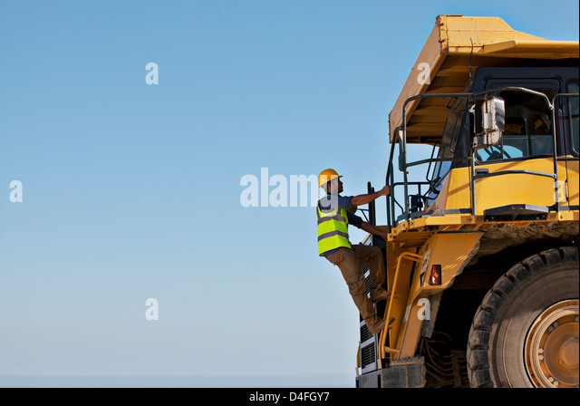Worker climbing machinery on site - Stock Image
