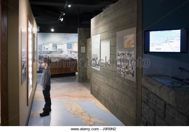 Curious boy viewing exhibit in war museum - Stock Image
