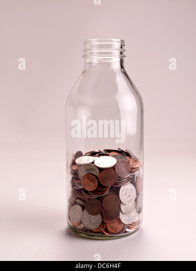 A half full jar of American coins sits on a white background. - Stock Image
