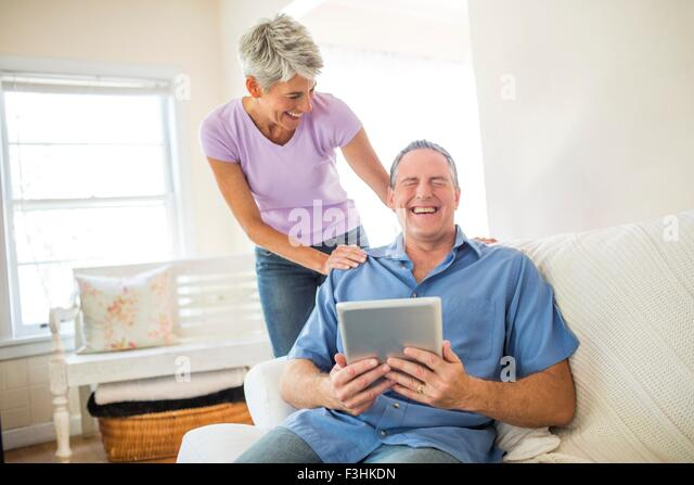 Mature couple laughing whilst using digital tablet - Stock Image