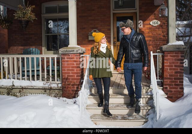 Couple leaving house in winter - Stock-Bilder