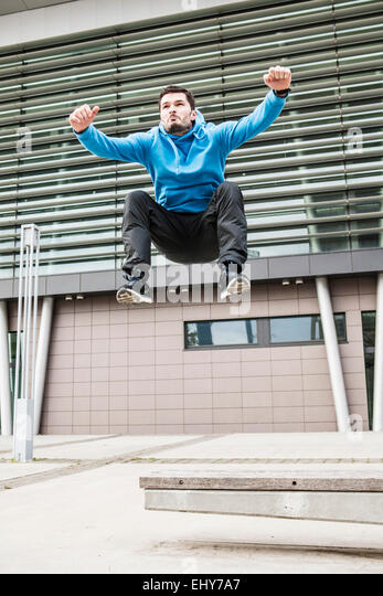 Male runner jumping arms raised - Stock Image