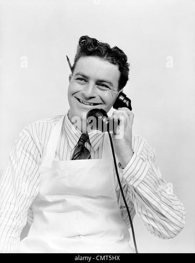 1930s PORTRAIT SMILING MAN CLERK WEARING APRON TALKING ON TELEPHONE PENCIL BEHIND EAR - Stock Image