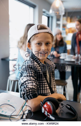 Portrait smiling,confident Caucasian high school boy student with headphones studying in cafe - Stock Image