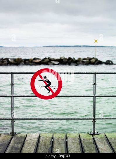 No swimming sign on pier railing - Stock-Bilder