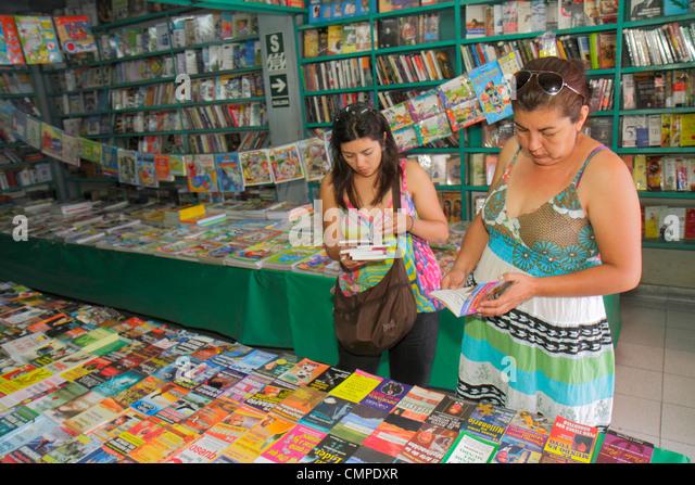Peru Tacna Avenida Francisco Bolognesi bookstore business shopping publishing Hispanic woman browsing book paperback - Stock Image