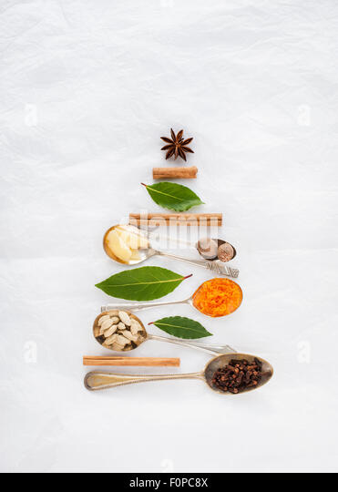 A Christmas tree shape made with spoons and spices cinnamon nutmeg star anis bay leaves cloves cardamom pods ginger - Stock Image