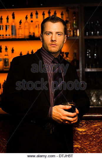 Handsome Young Man Cradling A Drink In Hands Standing At A Nightclub Bar In A Depiction Of Clubbing And Nightlife - Stock Image