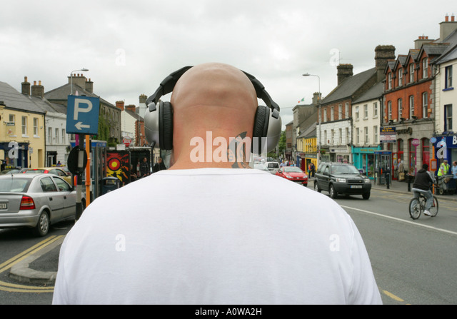 rear view of man with shaved head and tattoo wearing headphones - Stock-Bilder