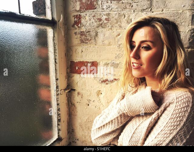 Beautiful young Caucasian blond woman looking out of the window smiling - Stock-Bilder