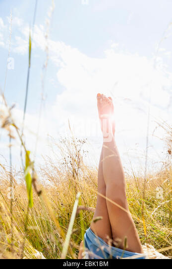 Young womans bare legs in field of long grass - Stock Image