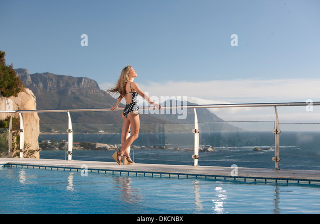 Woman enjoying view by swimming pool, Cape Town, South Africa - Stock Image
