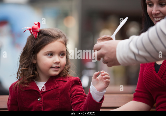 Girl sitting with her mother taking ice cream from her father - Stock Image