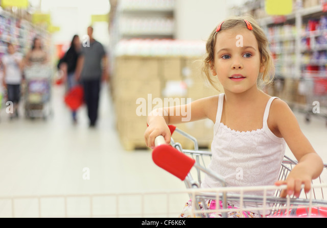 little girl sitting in store cart and looking at side, shelves with commodity - Stock Image