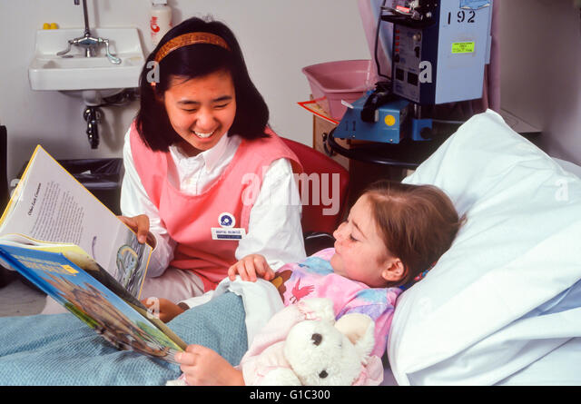 Teenage 16-17 years old Korean American Candystripper volunteer at bedside of very sick little girl 6-7-year old - Stock-Bilder
