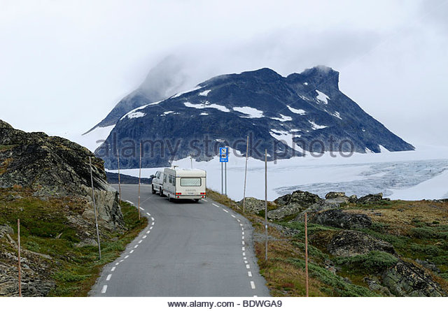 Minivan towing a caravan on a narrow road, mountains with snow, Sognefjell Pass road at Sognefjell Turisthytta, - Stock Image