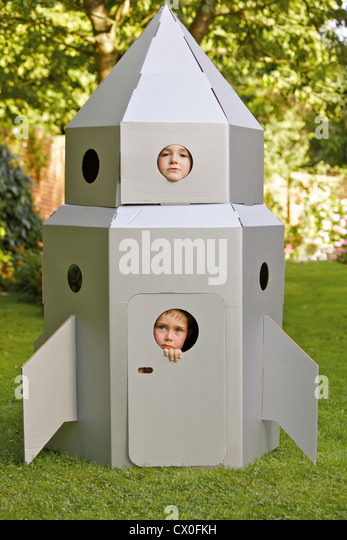 Two Boys Looking Out from Window of Cardboard Rocket Spacecraft - Stock Image