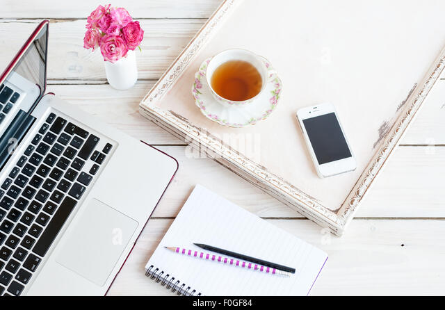 working from home - laptop, notebook, phone, pencils, tea and roses - Stock-Bilder