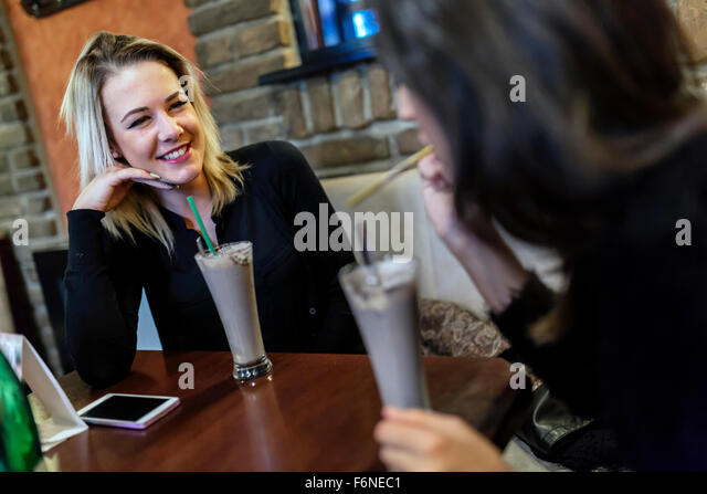 Two women drinking and talking in cafe while having a good time - Stock-Bilder
