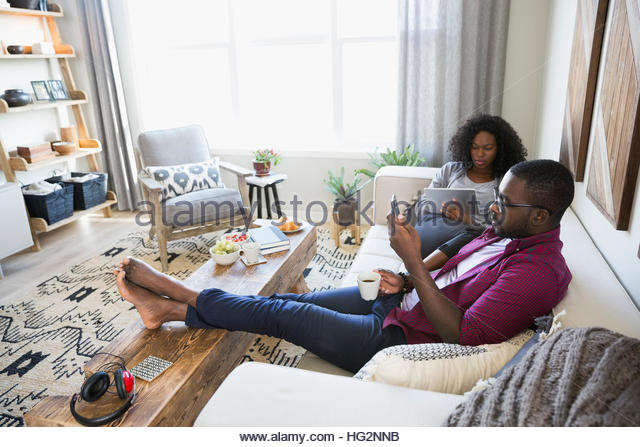 Couple drinking coffee using digital tablet and cell phone on living room sofa - Stock Image
