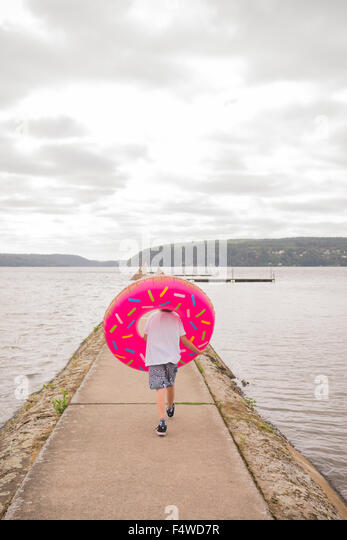 Sweden, Vastergotland, Lerum, rear view of boy (10-11) with inflatable ring on pier - Stock Image