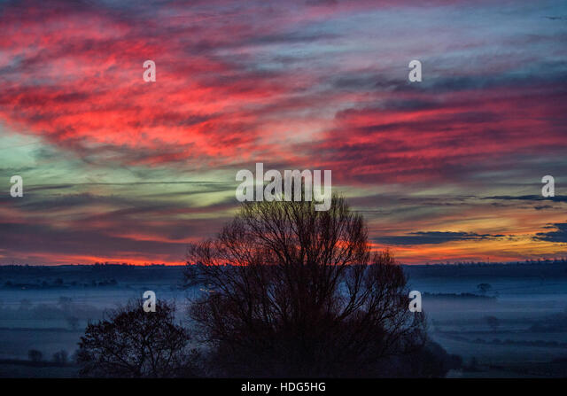 Burton Lazars, Leicestershire. 12th Dec, 2016.  Morning mist turns to dramatic sun rise over wolds. © Clifford - Stock Image