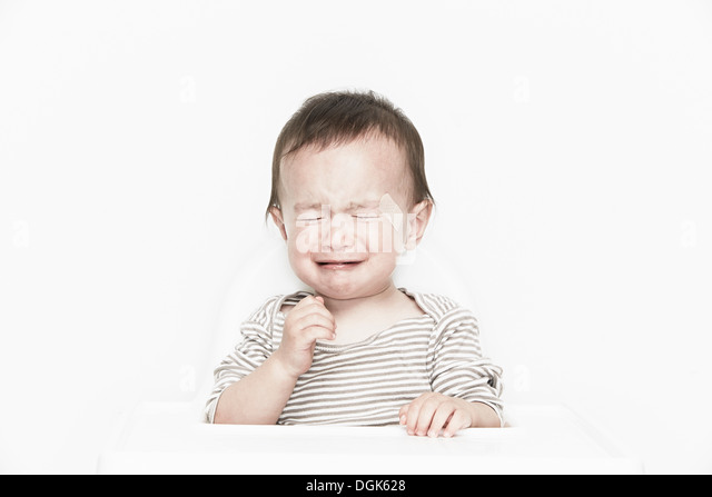 Baby boy with adhesive plaster on face, crying - Stock Image