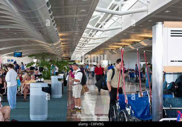 Travelers waiting at gates in Orlando International Airport in Orlando, Florida - Stock Image