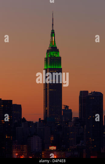 The Empire State Building is illuminated in green lights as the sky glows orange before sunrise in New York City. - Stock Image
