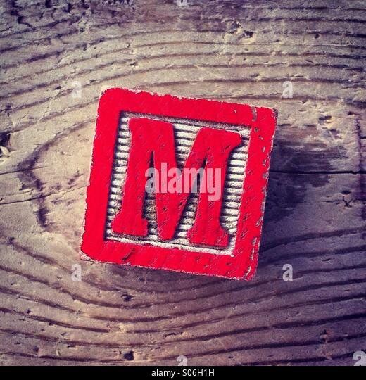 It's a woodblock toy with an alphabet letter on it: M - Stock Image