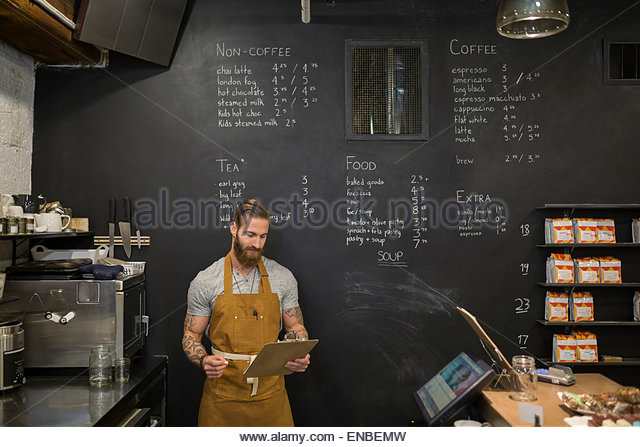 Hipster barista with clipboard in coffee shop - Stock-Bilder