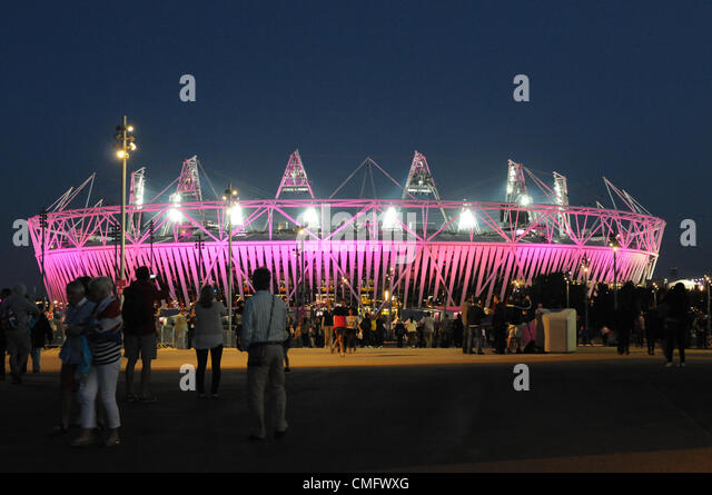Spectators gather to photograph the floodlit 2012 Athletics Stadium as dusk falls in the 2012 Olympic Park, London - Stock Image