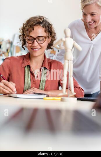 Female design professionals with artist?s figure sketching in office - Stock-Bilder