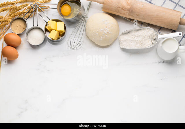 Baking cake, dough recipe ingredients (eggs, flour, milk, butter, sugar) on white table. - Stock Image