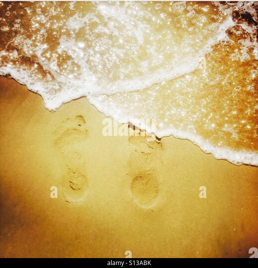 Water washing over footprints in the sand. Manhattan Beach, California USA. - Stock Image