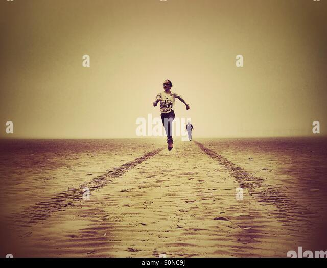 Two young girls having fun running on deserted beach between tyre tracks - Stock Image