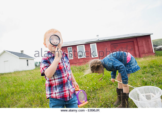 Curious boy with magnifying glass - Stock Image