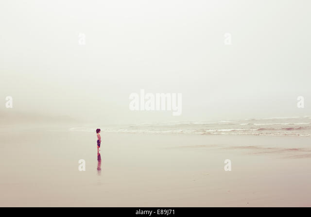 Boy at the ocean on overcast day - Stock Image