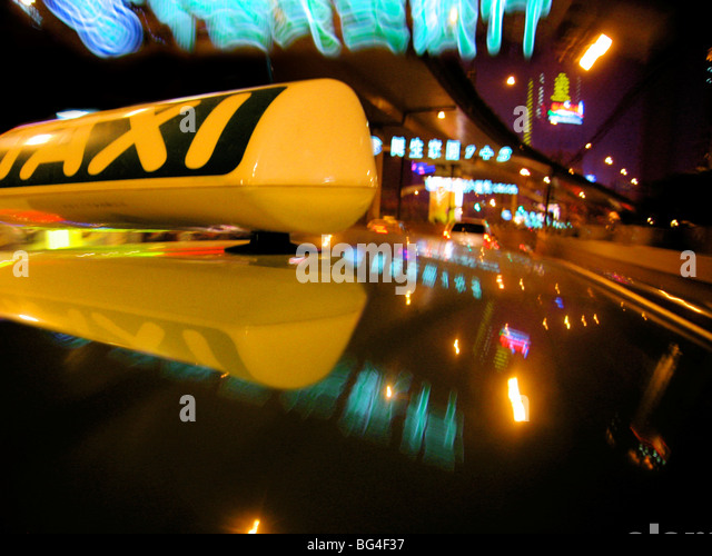 Close up of Taxi sign on car roof with neon road signs, Shanghai, China, Asia - Stock Image