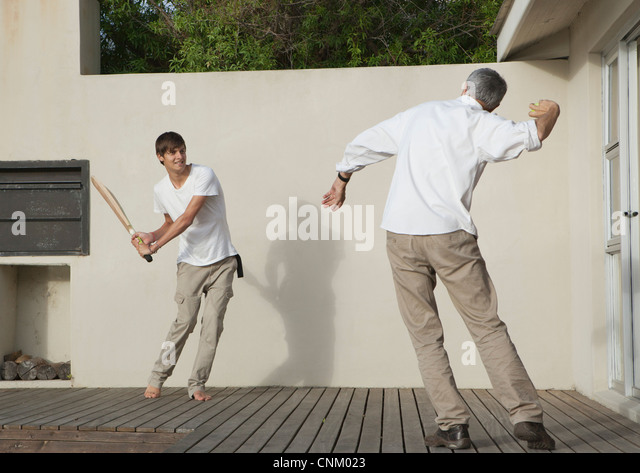 Father and son playing cricket on patio - Stock Image