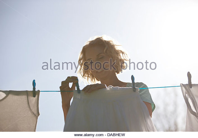A mature woman pegging out washing on a washing line, front view - Stock Image