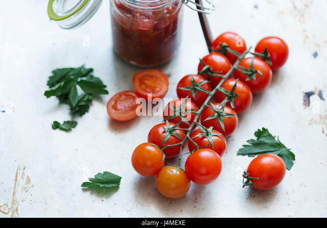 Tomatoes on vine near jar - Stock-Bilder