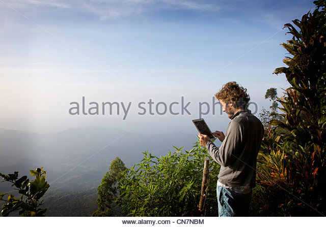 Man using tablet computer in jungle - Stock Image