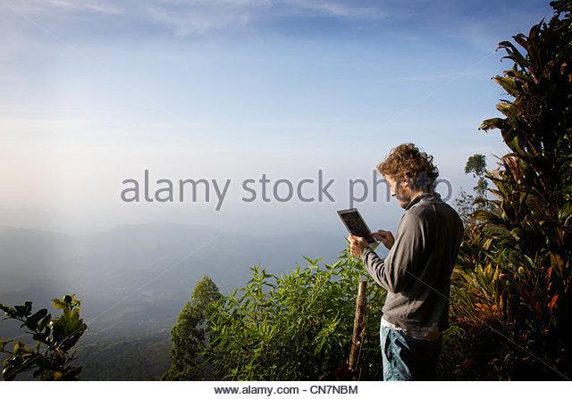 Man using tablet computer in jungle - Stock-Bilder