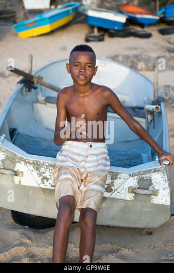 SALVADOR, BRAZIL - FEBRUARY 20, 2016: Young Brazilian leans against a traditional row boat resting on the shore - Stock Image