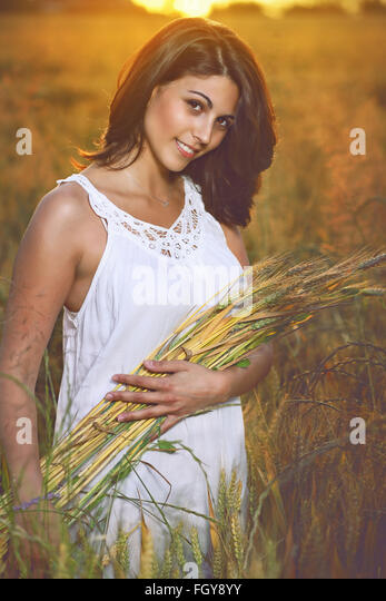 Beautiful woman in a golden cereal field surrounded by summer sunset light - Stock-Bilder