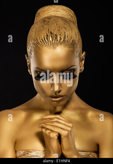 Belief. Styled Woman with praying hands. Golden Makeup - Stock Image