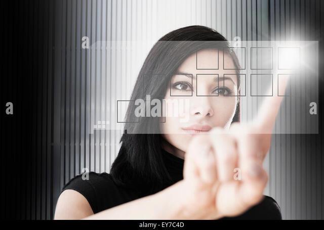 Woman touching screen button - Stock Image