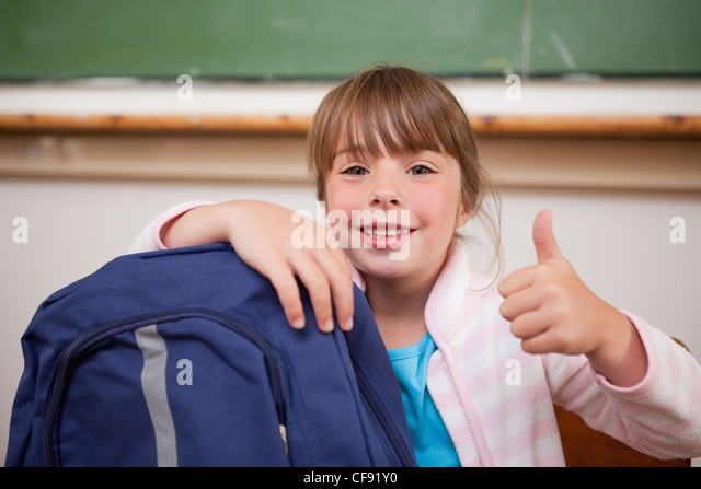 Smiling schoolgirl posing with a bag and the thumb up - Stock Image