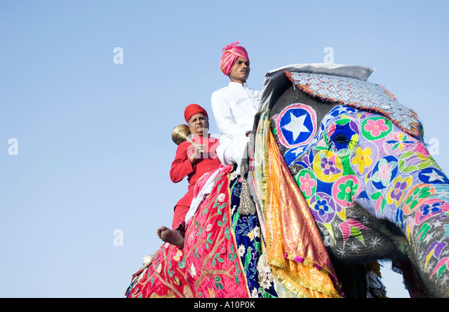 Low angle view of a young man and a senior man riding an elephant, Elephant Festival, Jaipur, Rajasthan, India - Stock Image